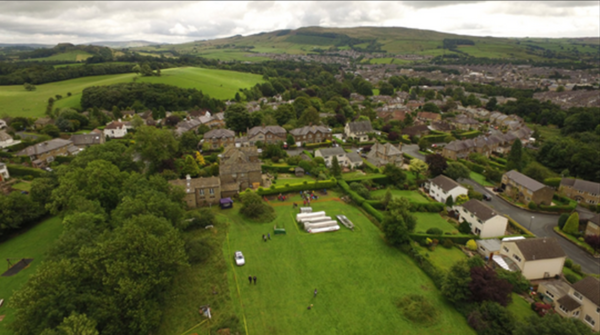 aerial photograph showing field in foreground where archaeological dig took place. Houses and hills in background
