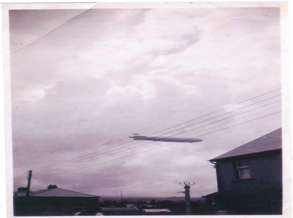 hindenburg airship flying over houses