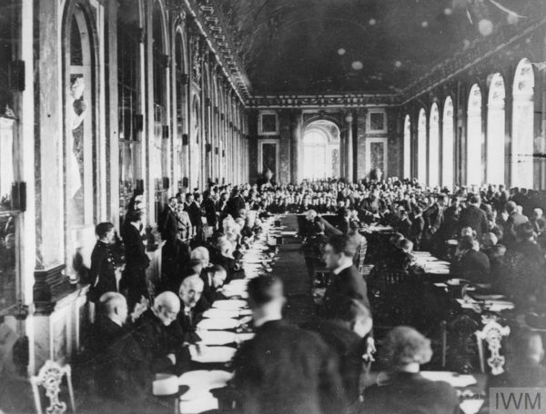 photo showing men sat around long tables in hall of palace at first world war peace treaty conference